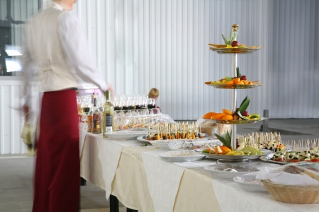 Served banquet table with small fancy cakes and fruits photo