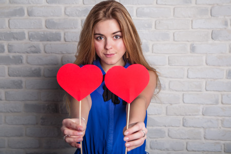 The girl holds in the hands of cut heart cardboard