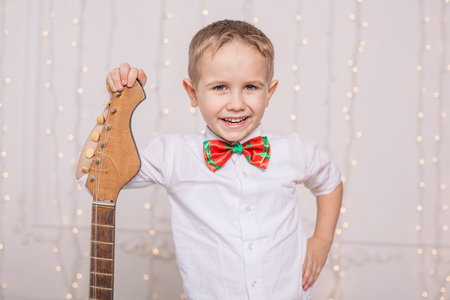 Cheerful boy in his room with his favorite guitar Фото со стока