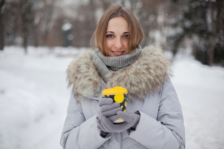 Woman holding hot drink in the snow park 写真素材