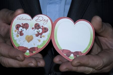 hand holding playing card: Hands of a man in a suit with heart postcard. Valentines Day