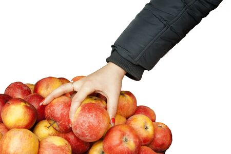 A female hand in a jacket takes an apple.