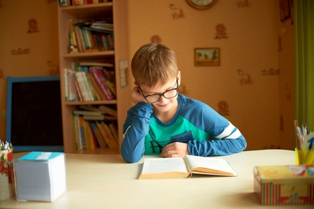 occupied: boy reading a book fully occupied. Boy in glasses reading a book doing homework study
