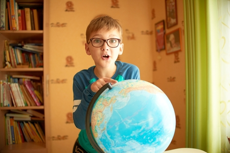 sees: Boy with a globe. The boy in the glasses sees the globe
