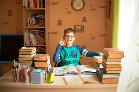 bored student: education, childhood, people, homework and school concept - bored student boy reading book or textbook at home