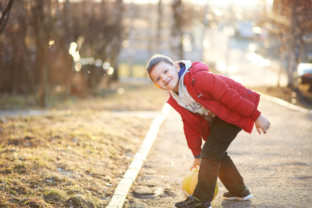 plays: boy in a red jacket, pants, sneakers plays soccer, enjoys running, kicking the ball, smiling Stock Photo