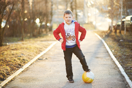 running pants: boy in a red jacket, pants, sneakers plays soccer, enjoys running, kicking the ball, smiling Stock Photo