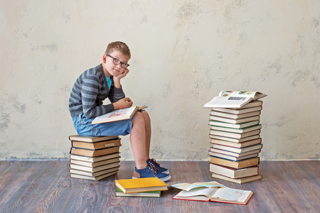 The boy student in sneakers shorts and a sweater sitting on a stack of books and reading. On a yellow colored background. Educational concept Stock Photo