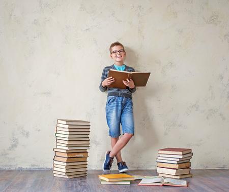 bermudas: El estudiante del muchacho en pantalones cortos y zapatillas de deporte un suéter que se sienta en una pila de libros y la lectura. Sobre un fondo de color amarillo. concepto de formación