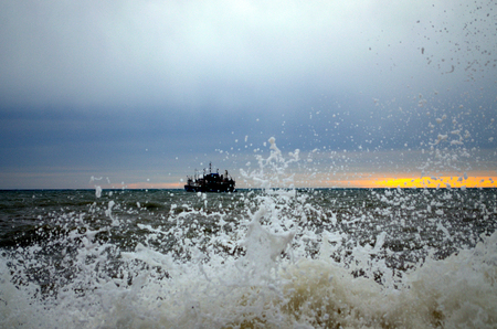 Ship in bad weather at sea at sunset. Storm wave in the foreground. Splashing water. Foamy surf