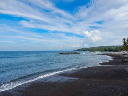 Sea beach with black volcanic sand with a strip of greenery in the distance and clouds in the blue sky Фото со стока