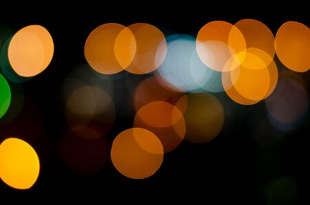 Bokeh of defocused night lights of yellow, red and blue colors on a black background.