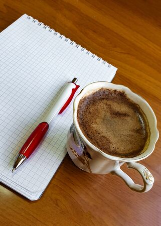 Porcelain coffee cup with foam on the office desk, a blank notepad page and a pen - diagonal arrangement of objects in the frame