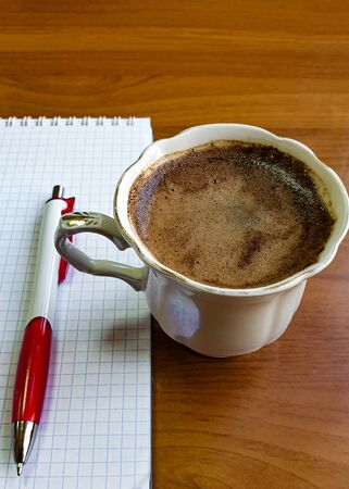 Porcelain cup with foam on the office desk, a blank notepad page and a fountain pen - side view