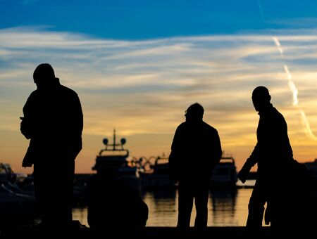 Dark silhouettes of a group of people on the sea pier of the yacht marina against the sunset, silhouettes of yachts and blue sky Фото со стока