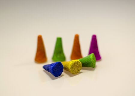 Aromatic cones for incense of different colors stand on a white surface. Partially scattered on the table