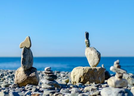 The figure of stones standing on each other, on the beach against the sea. Fun and relaxation on the beach Фото со стока