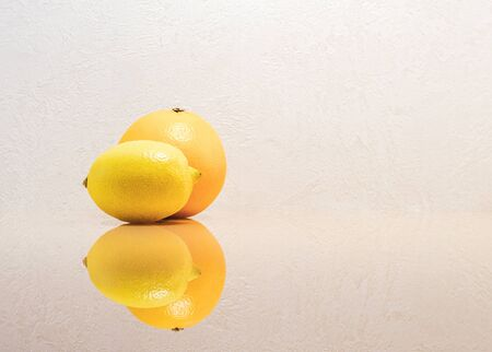 Orange, lying behind a lemon, on a bright white background with a reflection on the glass surface. Frontal image with negative empty space Фото со стока
