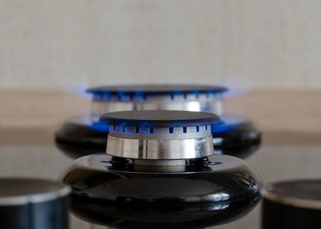 Two gas burners with a flame on a glass surface. Kitchen stove on a background of ceramic tiles. Frontal image with blurred foreground and flame adjustment knobs Фото со стока