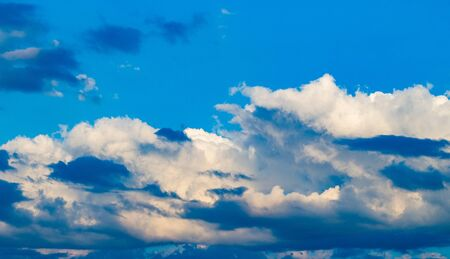 Clouds with shades and shadows against a blue sky, illuminated by the morning sun for half a frame. Patterns of cumulus clouds of different colors.