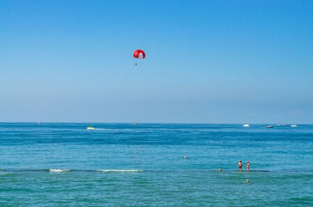 Beach activities in the sea: parasailing, yachts on the water, people in the sea, waves. Outdoors Фото со стока