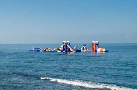 Inflatable water park in the sea with the oncoming wave in the foreground. Beach activities Фото со стока