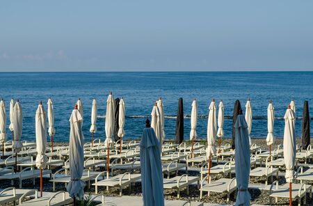 Folded beach umbrellas and loungers lit by the morning sun on the background of the sea