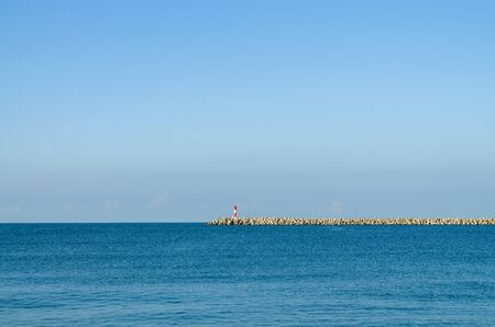 Sea pier on the horizon. Calm sea surface and clear sky without clouds Фото со стока