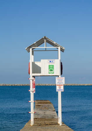 Lifeguard tower on the breakwater against the backdrop of the sea and the pier. Vertical frame
