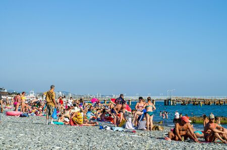 Sochi, Russia - July 7, 2019: Pebble beach, many tourists sunbathe
