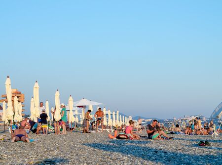 Sochi, Russia - July 7, 2019: People on the beach of Dagomys in the evening Редакционное