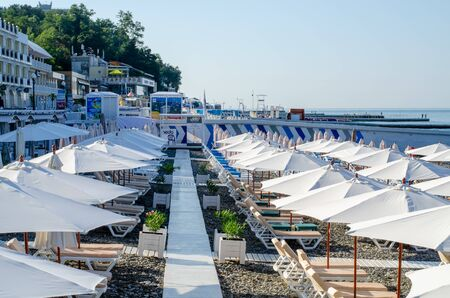 Sochi, Russia - July 20, 2019: Beach umbrellas and sun beds in the early morning on the beach