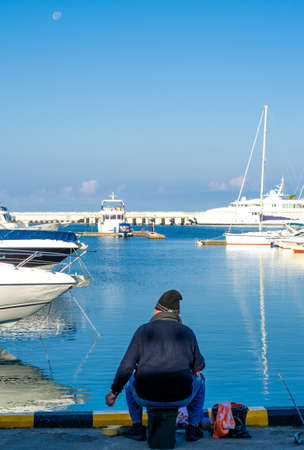 Fisherman in old clothes on the pier on the background of yachts with reflection in the water