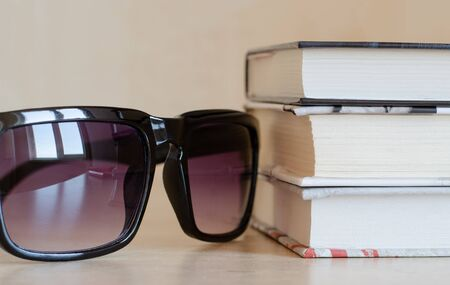 Sunglasses with a reflection of the window and a stack of books at an angle. Snapshot krypnom plan. A set of items for reading on vacation Imagens - 132071487