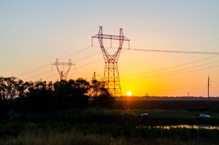 Pylons of a high voltage power line in a field by the river at dawn, wires and poles. Orange sun over the steppe. The sky is pink. Fishermans machines by the water Фото со стока