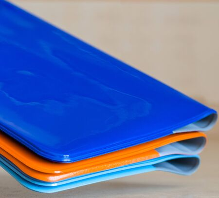 Roots of multi-colored shiny passport covers at an angle in the air. Close-up shot