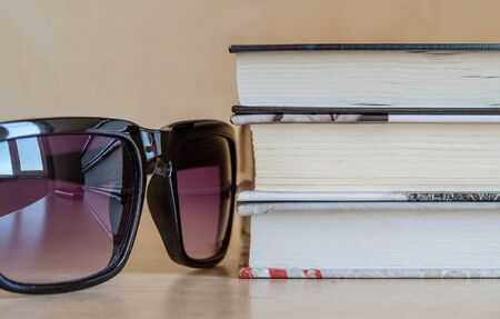 Sunglasses with a reflection of the window and a stack of books. Snapshot krypnom plan. A set of items for reading on vacation