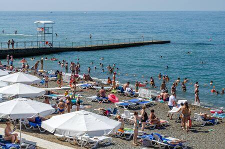 Sochi, Russia - July 20, 2019: Tourists bathe and sunbathe on the beach