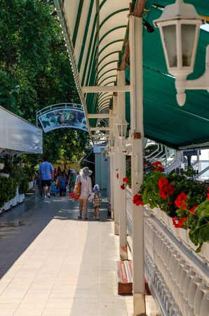 Sochi, Russia - July 20, 2019: The facade of the beach cafe on the seafront. Fence with red geranium flowers and street lamps