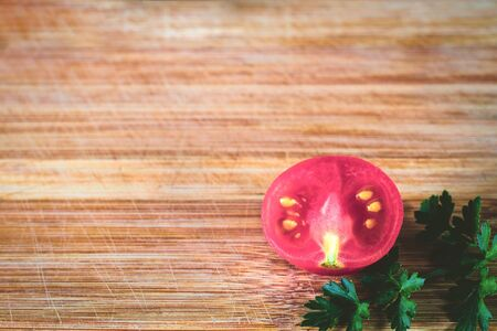 Half sliced tomato on a sprig of parsley, in warm soft shades, on a wooden surface. Top view at an angle