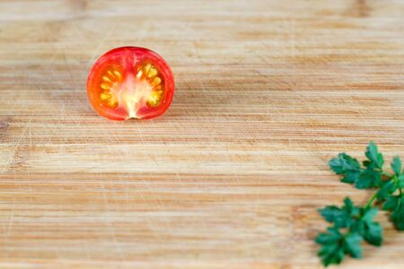 Half a tomato at the top of the frame and part of a sprig of parsley at the bottom. On a wooden surface. Top view at an angle