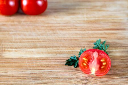 Half sliced tomato on a sprig of parsley and two tomatoes on top in the corner, on a wooden surface