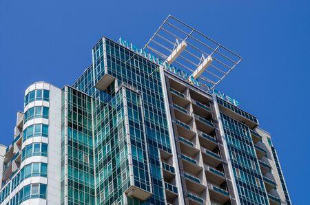 Sochi, Russia - July 20, 2019: residential complex Millennium Tower. Facade of modern green glass building, bottom view