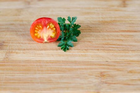 Half a tomato and a sprig of parsley on a wooden surface at the top of the frame. Top view at an angle