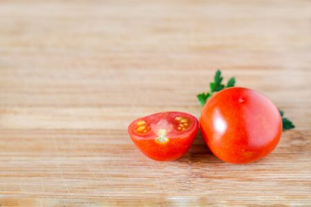 Shiny tomato and half a tomato on a sprig of parsley on a wooden surface. Top view at an angle Stockfoto