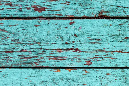 Background of three old boards with peeling turquoise paint, close-up
