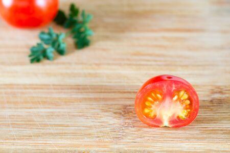 Half a tomato on a blurry background from tomato and parsley on a wooden surface. Top view at an angle