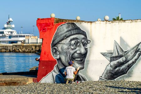 Sochi, Russia - July 20, 2019: artist paints graffiti with Jacques Yves Cousteau on the concrete structure of the sea beach. Overall plan