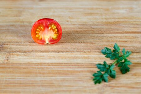 Half a tomato at the top of the frame and a sprig of parsley at the bottom. On a wooden surface. Top view at an angle Stockfoto