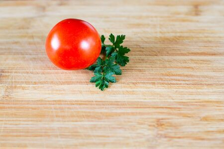 Shiny tomato and a sprig of parsley on a wooden surface at the top of the frame. Top view at an angle
